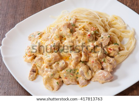 Sliced fried chicken meat in a creamy sauce with spaghetti pasta in a plate on wooden table