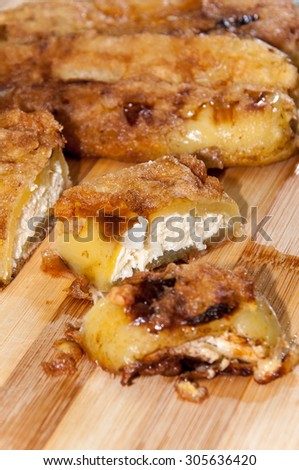 Sliced fried stuffed paprika with cheese on the wooden board.
