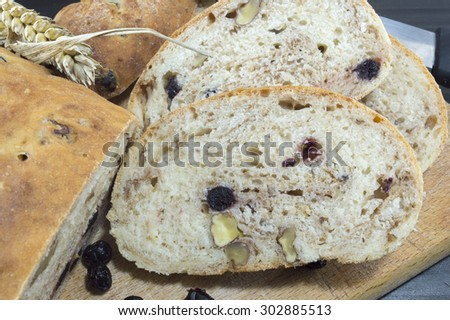 Sliced fruit bread with aronia and nuts on a wooden plate with dried aronia decoration
