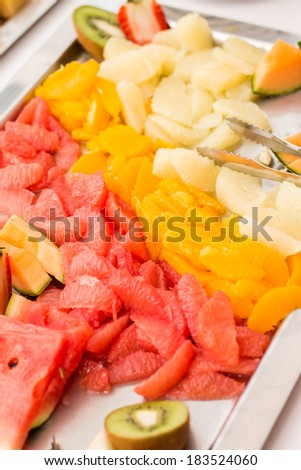 Sliced fruit platter on stainless steel tray - stock photo