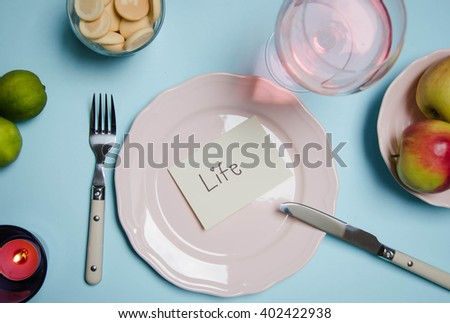 Sliced fruits and berries on plate with glass of water on table on wooden background
