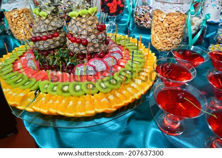 Sliced fruits and glasses of cherry juice on dessert table - stock photo
