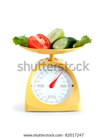 Sliced fruits and vegetables on kitchen scale. Isolated on white with clipping path - stock photo
