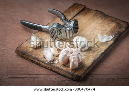 sliced garlic, garlic clove, garlic bulb in wicker basket place on chopping block on vintage wooden background with garlic crusher - stock photo