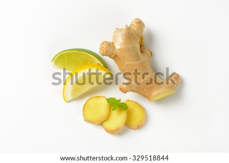 sliced ginger with lemon and lime on white background - stock photo