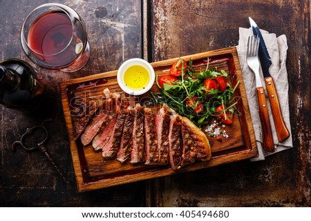Sliced grilled beef barbecue Striploin steak and salad with tomatoes and arugula on cutting board and wine on dark background