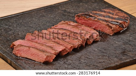 Sliced grilled beef steak on stone board. - stock photo