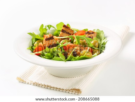 Sliced grilled patty on nest of rocket salad with tomato and olives