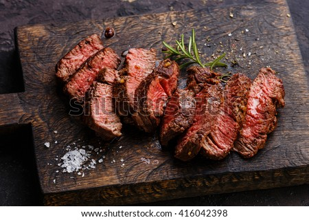 Sliced grilled steak roastbeef and rosemary on wooden cutting board background - stock photo