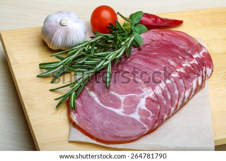 Sliced Ham with herbs on the wood background - stock photo