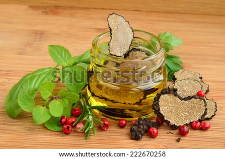 Sliced heart shaped black truffle in olive oil in small jar and some fresh spices, basil, oregano, rosemary and red pepper - stock photo