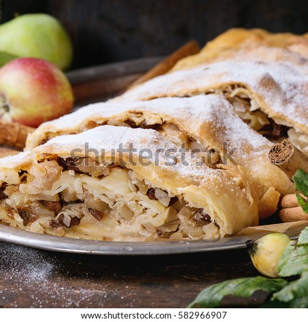 Sliced homemade apple strudel served with fresh apples with leaves, cinnamon sticks and sugar powder on vintage metal tray over old wooden background. Close up, dark rustic style. Square image