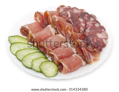 Sliced homemade dry sausages and meat products, cured meat, bacon, with fresh cucumber slices on a white plate. Isolated on white background, close-up, top view. - stock photo