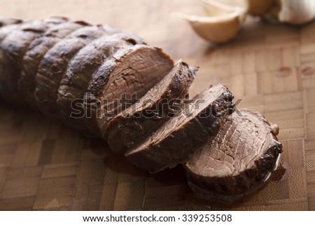 Sliced juicy beef tenderloin on wooden plate - stock photo