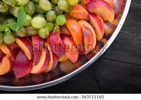 sliced juicy peach on dish - stock photo