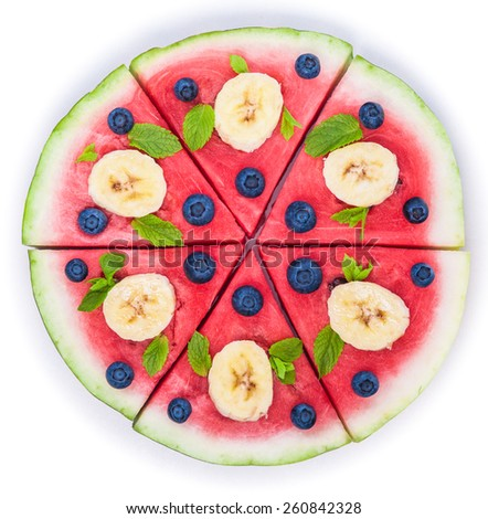 Sliced juicy watermelon pizza isolated on white, closeup view from above. Ingredients are watermelon, blueberries, banana, mint. - stock photo