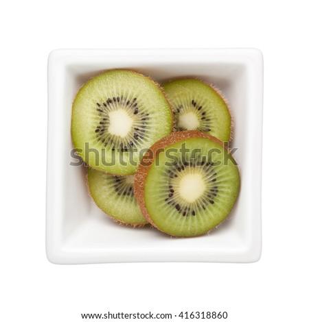 Sliced kiwifruit in a square bowl isolated on white background - stock photo