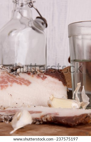 Sliced lard on a wooden desk with onion,  vodka and bread