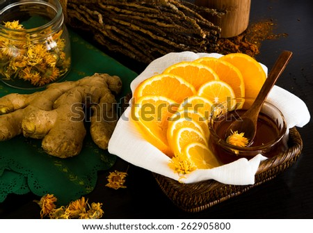 Sliced lemon and orange in basket with honey, dry calendula, branches and ginger root behind - stock photo