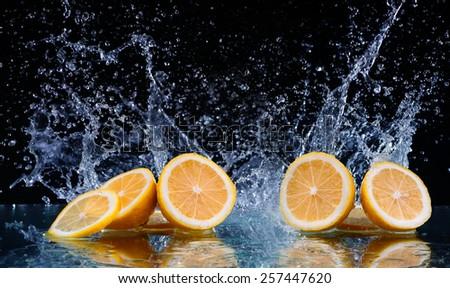 Sliced lemon in the water on black background - stock photo