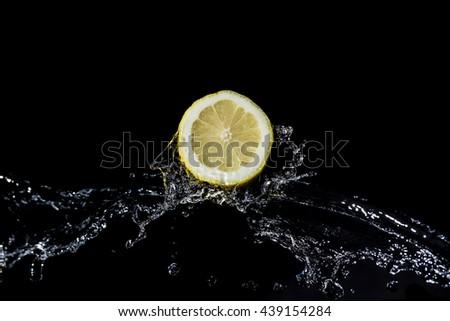 Sliced lemon with water splash on black background - stock photo