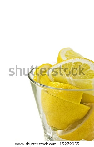 Sliced lemons stacked in a glass against a white background.