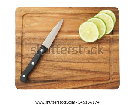 Sliced lime and black knife on wooden cutting board isolated - stock photo