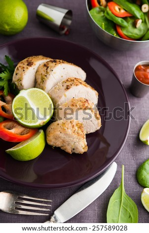 Sliced lime pork tenderloin and fresh healthy spinach salad on dark background. Healthy food. - stock photo