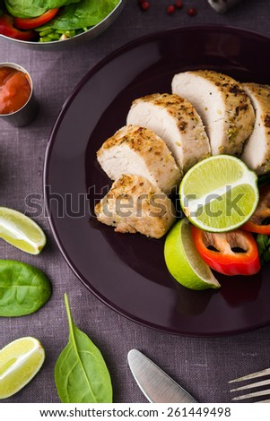 Sliced lime pork tenderloin and fresh healthy spinach salad on dark canvas background top view. Healthy food. - stock photo