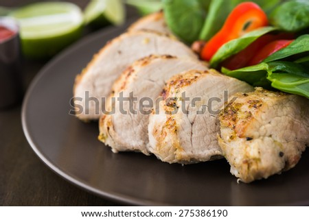 Sliced lime pork tenderloin with vegetables salad on dark wooden background close up.  Healthy food. - stock photo