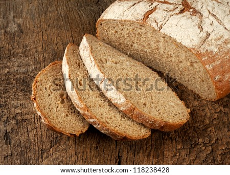 Sliced loaf of rye bread on rustic wooden background - stock photo