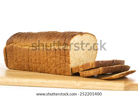 Sliced loaf of whole wheat bread on cutting board - stock photo