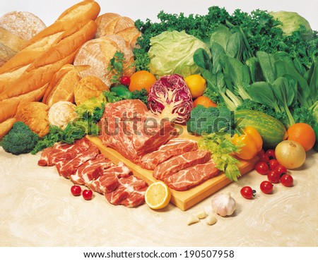 Sliced meat, various breads and fresh vegetables - stock photo