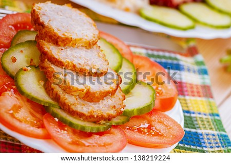 Sliced �¢??�¢??meatballs with cucumbers and tomatoes in white bowl on checkered napkin. - stock photo