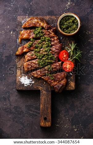 Sliced medium rare grilled beef barbecue Sirloin steak with chimichurri sauce on cutting board on dark background - stock photo