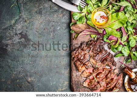 Sliced medium rare grilled beef  barbecue steak with fresh green salad and cutlery on rustic background, top view, place for text. Meat food - stock photo