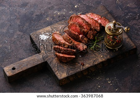 Sliced medium rare grilled Beef steak and pepper mill on wooden cutting board  - stock photo