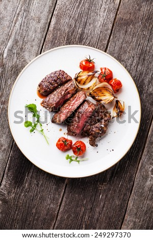 Sliced medium rare grilled Beef steak Ribeye with grilled onions and cherry tomatoes on plate on wooden background - stock photo