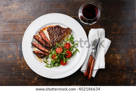 Sliced medium rare grilled Beef steak Striploin, salad with tomatoes and arugula on white plate and red wine on dark wooden background - stock photo
