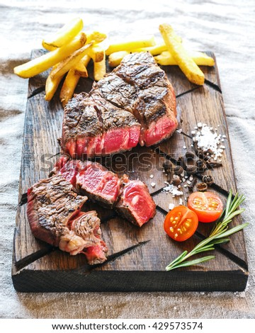 Sliced medium rare grilled beef steak with french fries, salt, pepper, tomato and rosemary on meat cutting board - stock photo