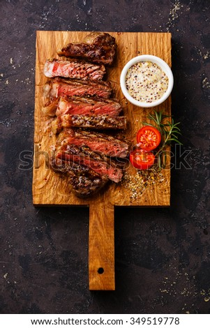 Sliced medium rare grilled Sirloin steak and Pepper sauce on cutting board on dark background - stock photo