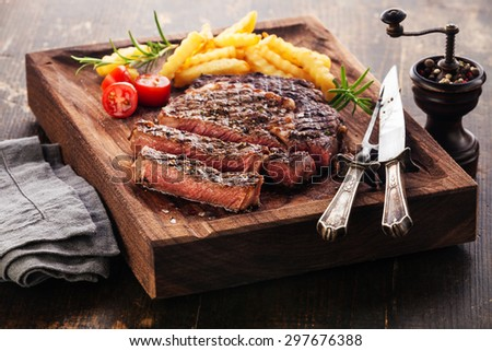 Sliced medium rare grilled Steak Ribeye Black Angus with french fries on serving board block on wooden background - stock photo
