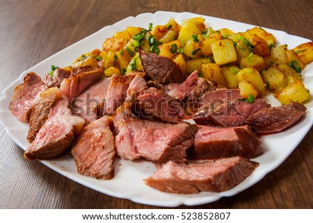 Sliced medium rare grilled Steak Ribeye with potato in a plate on wooden table