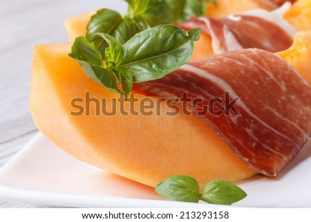 sliced melon wrapped in prosciutto and green basil on a white plate on the table. horizontal macro  - stock photo