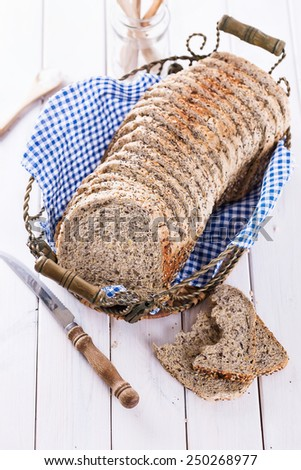 Sliced multigrain sandwich bread loaf in a metal basket on white wooden table