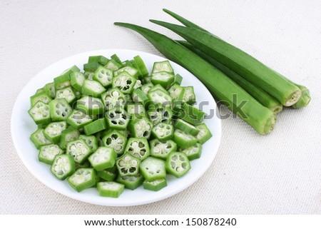sliced okras with raw okras. - stock photo