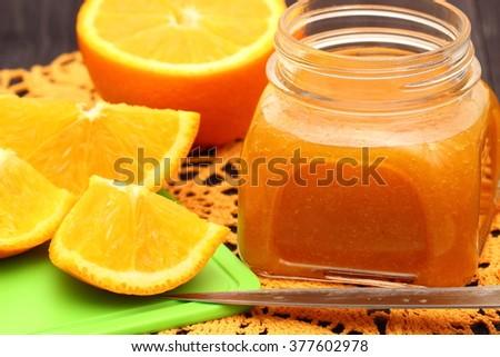 Sliced oranges and orange jam in glass jar - stock photo