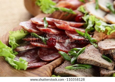 sliced peaces of meat on wooden tray - stock photo