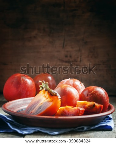 Sliced persimmon on a plate, selective focus - stock photo