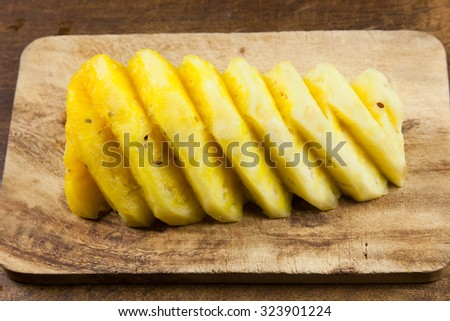 sliced pineapple on a wooden board - stock photo
